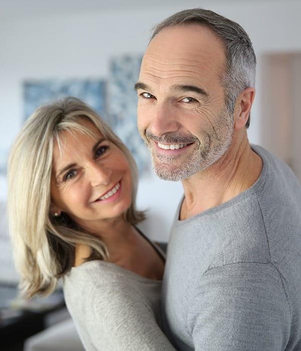 Smiling couple with dental implants in Greensboro