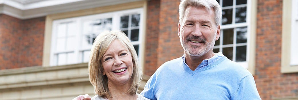Smiling, happy couple with dental implants in Greensboro