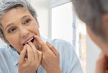 Woman flossing to care for dental implants in Greensboro