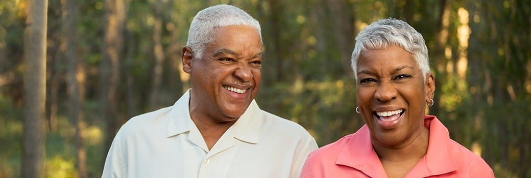 a man and a woman smiling with implant retained dentures