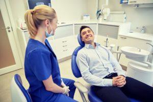man in dress shirt smiling at dentist in Greensboro